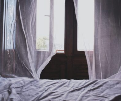white bedspread beside window