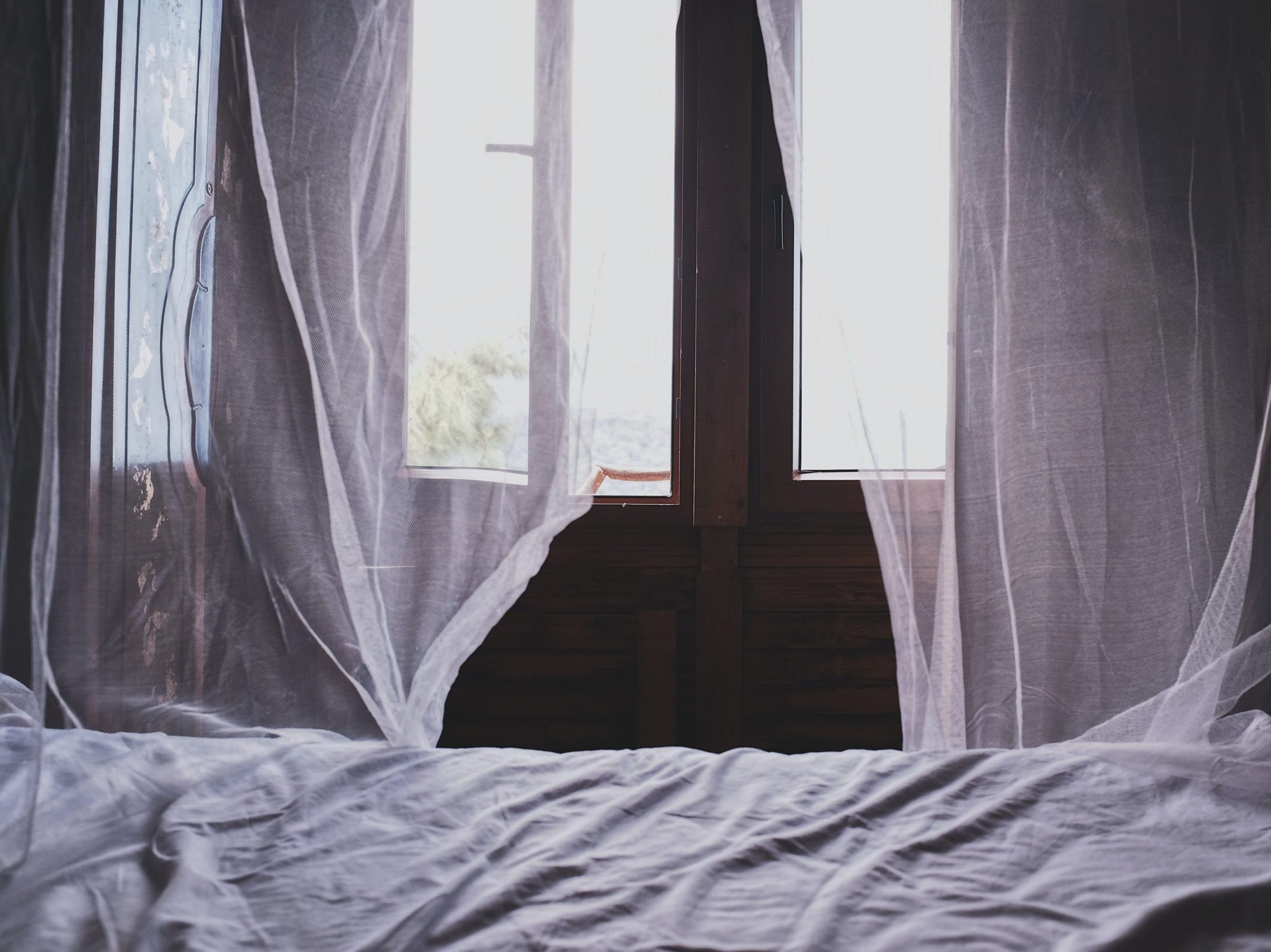 white bedspread beside window