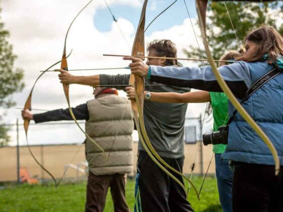 three person practicing using arrow