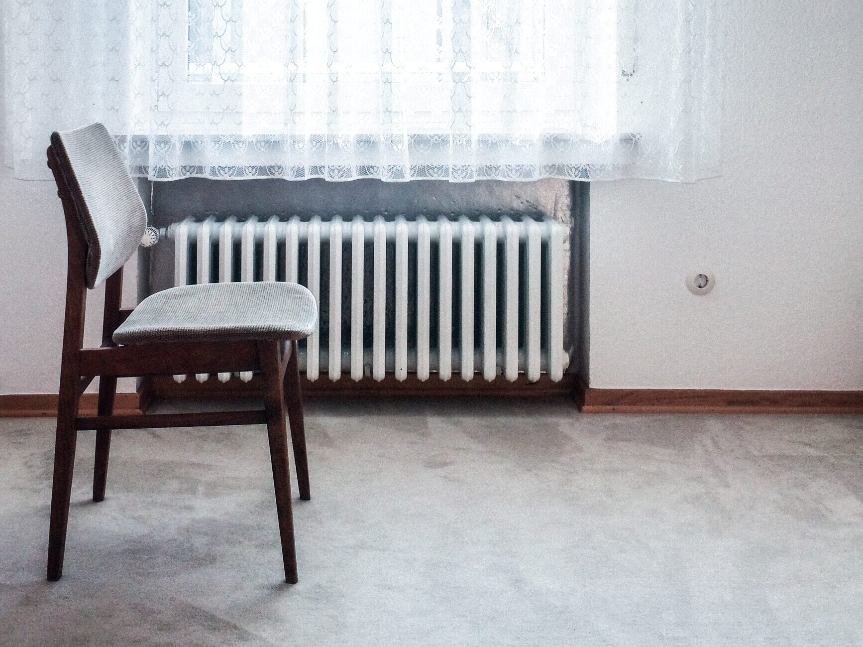 brown chair beside white radiator heater