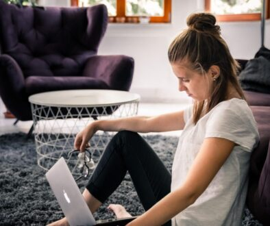 woman in white t-shirt and black leggings sitting on area rug while facing silver MacBook